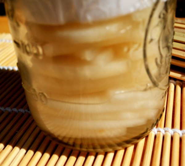 Water collecting in the jar as it presses out of daikon.